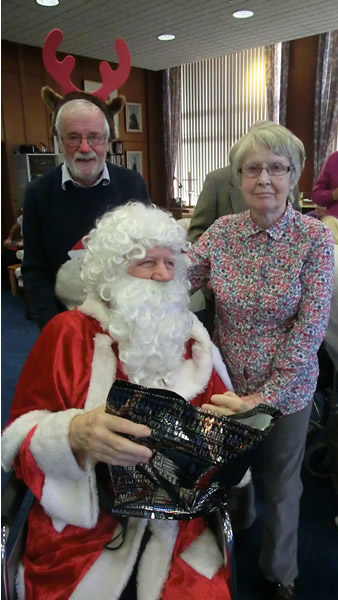 "WBro Michael ""Rudolph"" Robinson with Santa and a Devonshire Court resident"
